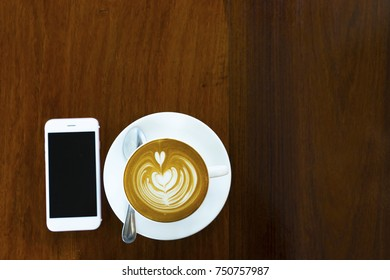 A cup of hot latte art coffee and smart phone on wooden background. Hot white cup of coffee with heart shape on wood table from top view.