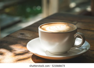 A cup of hot latte coffee on vintage wooden table in cafe