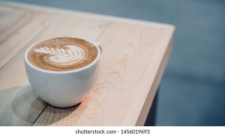 a cup of hot latte coffee with rosetta latte art
