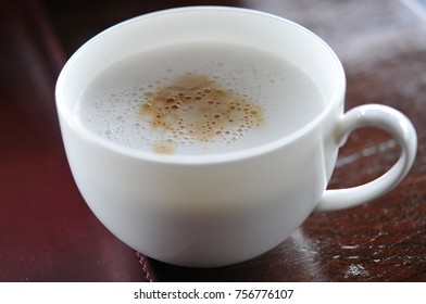 A cup of hot Latte coffee in a white cup on wooden table background.