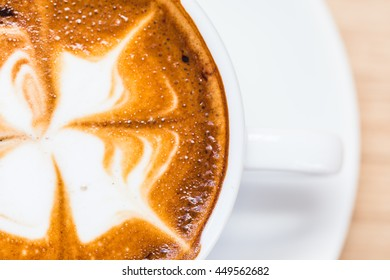 A cup of hot mocha coffee with flower pattern in a white cup on wooden background