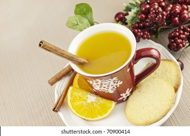 A cup of hot spiced fruit Wassail holiday punch with a cinnamon stick and homemade sugar cookie
