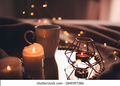Cup of hot tea with burning candles on tray in bed over Christmas lights close up. Night time atmosphere at home.  - Shutterstock ID 1849397386