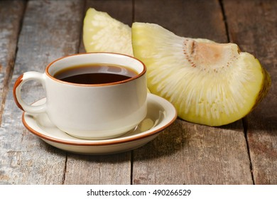 a cup of hot tea, with cooked breadfruit slices on wooden table