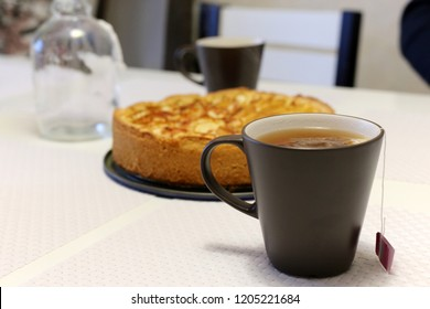 A cup of hot tea with delicious homemade apple pie. Dark grey teacup with a tea bag in and a crunchy apple pie in the background. Perfect fall or Thanksgiving treat! Light and mostly warm colors.