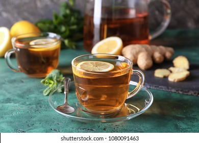 Cup of hot tea with ginger and lemon on table