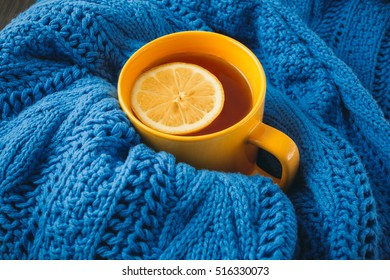 Cup of hot tea with lemon dressed in knitted warm winter scarf, warm knitted sweater or blanket. still life of a scarf and Cup of tea with lemon. Winter time. Cozy and soft winter background.