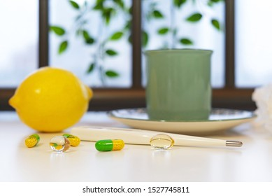 A cup of hot tea with a lemon as a natural way for healthcare and treatment concept during a flu on a rainy autumn day; thermometer, pills, paper wipes and plant on the background of the window