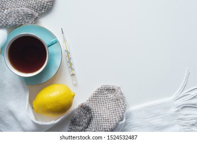 Cup of hot tea, lemon, thermometer and scarf on white table flat lay background.