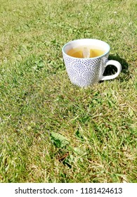 A cup of hot tea on a garden lawn.