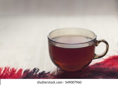 A Cup of hot tea is on the warm scarf on the background of wooden boards, comfort, rest, relaxation, holidays, vacation