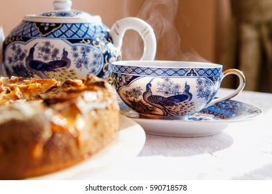 A cup of hot tea, a tea pot and a part of an apple pie on a table covered with a white tablecloth. Cozy breakfast.