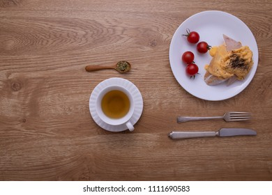 A cup of hot tea put with a dish of breakfast, egg, ham and tomato with fork and knife on brown wood texture table.