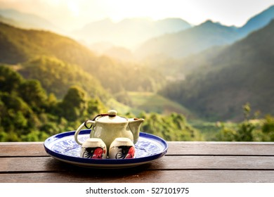 Cup of hot tea with sacking on the wooden table and the tea plantations background , The Time of Tea Break , Teapot on table over mountains landscape with sunlight. Beauty nature background