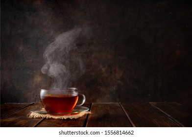 Cup of hot tea with a steam on dark rustic background. Copy space