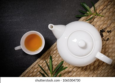 Cup of hot tea with steaming jugs and dry tea on the plate mat on the black stone table background with copyspace for your text.