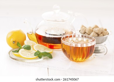 cup of hot tea tea, sugar, mint and lemon on a light background