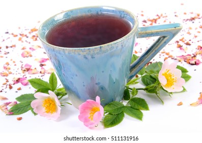 Cup of hot tea with wild rose, fresh blooming flowers and dried petals with tea grains on white background