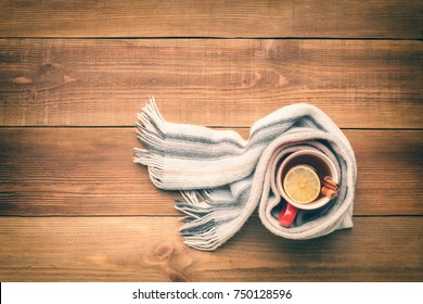 A cup of hot tea is wrapped in a woolen scarf. There is a lemon and two cinnamon sticks in the cup. Top view. Space for text.