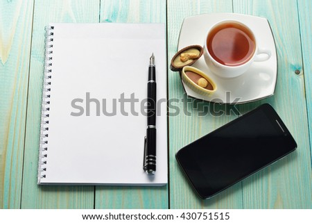 Cup Of Hot Tia Sweets Notepad And Pen On A Blue Wooden Table