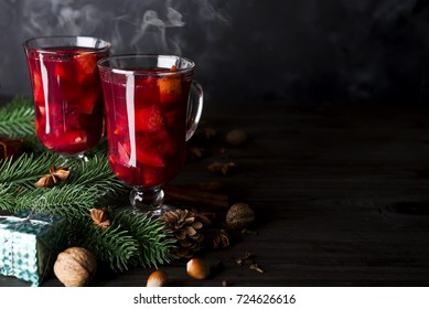 Cup of hot wine with spices with fir branches on a wooden dark background copy space