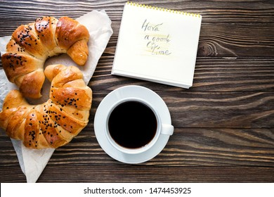 a cup of instant coffee with a croissant and message have a good time on the textured wooden background top view, cozy and delicious breakfast.