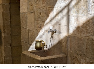 A cup for Jewish Handwashing Ritual next to sinagogue entry