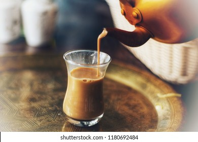 A Cup of Karak Tea Poured from a Kettle