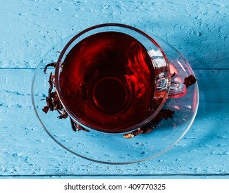 Cup of Karkadeh Red Tea with Dry Flowers on a blue wooden table