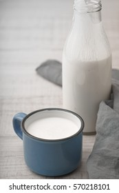 Cup with kefir, a bottle and napkin on a wooden table vertical