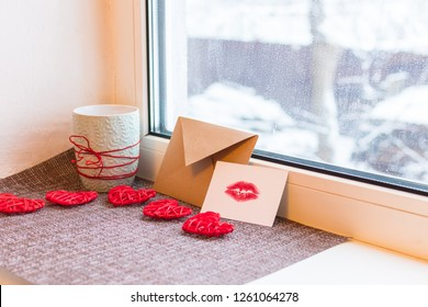 Cup, Kraft envelope, card with lip print and hearts on the windowsill. concept of Valentine's day
