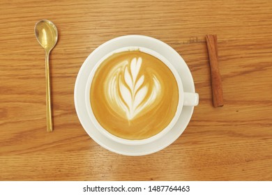 a cup of latte art coffee on wooden background