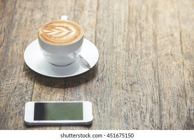 cup of latte art coffee and smart phone on wood table