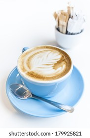Cup of latte art on a cappuccino coffee in blue cup