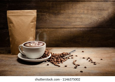 A Cup of latte art with paper bag of roasted coffee bean