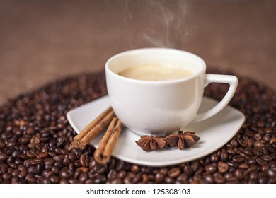 Cup of latte or cappuccino with cinnamon and anise, focus on cinnamon