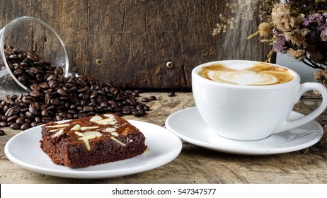 A cup of latte, cappuccino or espresso coffee with milk put on a wood table with dark roasted coffee beans and a piece of chocolate brownie cake