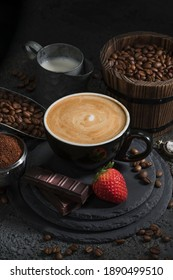 Cup of latte with chocolate, strawberry, milk, and coffee beans in a dramatic setup