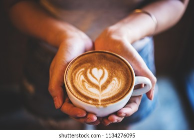A cup of latte coffe in woman hand