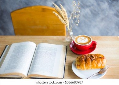 A cup of latte coffee on red cup with bread on table and open book in reading time