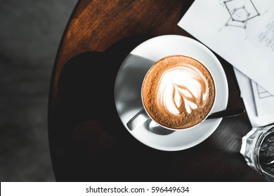 cup of latte coffee on wooden table with business document