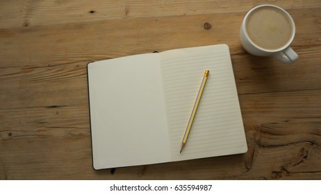 A cup of Latte milk coffee / cappuccino put on the wooden beside by a pencil on the notebook which has line, brown color tone as vintage and classic, all on desk in the working space