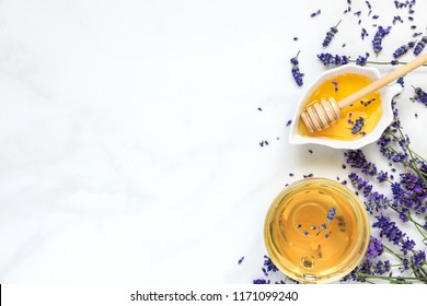 cup of lavender tea with honey and fresh flowers over white marble table. herbal drink. top view with copy space