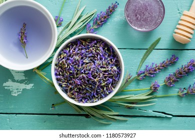 cup of lavender tea with a pile of flowers, syrup, candy sugar and dipper on blue wood table