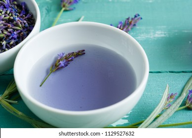 cup of lavender tea with a pile of fresh flowers, syrup, bunch, on blue wood table background