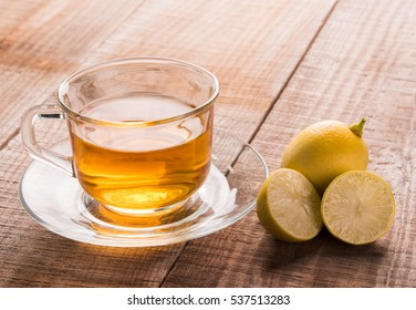 A cup of lemon tea and lemon on wooden background