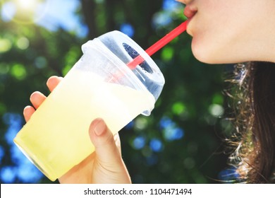 A cup of lemonade during a hot summer day in the hands of a girl, selective focus in top of dropped glass. The mouth of a girl who drinks at straw a cold lemonade in high summer temperatures.