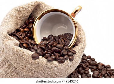 The cup lies in a sack with coffee grains is isolated on white