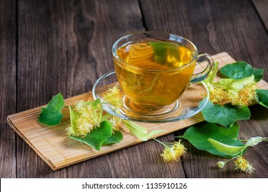 A cup of lime tea, standing on a wooden table, surrounded by fragrant linden flowers, in the rays of sunlight.