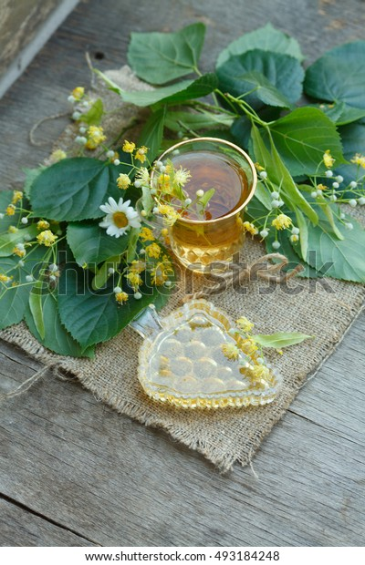 cup of linden tea with plate of linden honey with linden leaves and flowers on canvas and wooden background